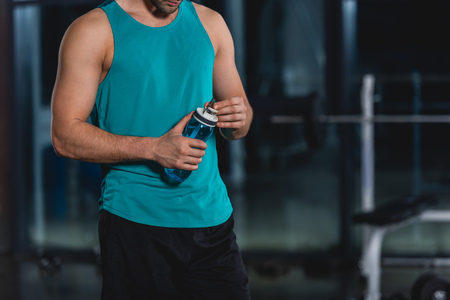 cropped view of sportsman holding sport bottle with water in gym