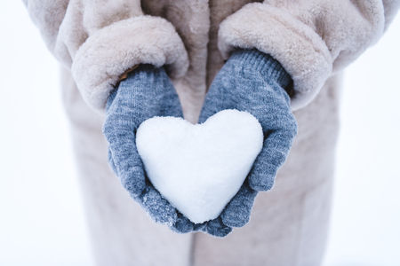 cropped shot of person holding heart symbol made from snow