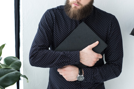 cropped shot of stylish businessman with notebook in hands