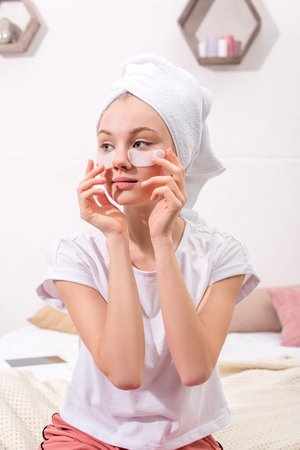 attractive woman spplying cosmetic facial patches at home Foto de archivo - 112756404
