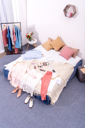 high angle view of interior of modern bedroom with hanger full of various female clothing and makeup supplies on bed