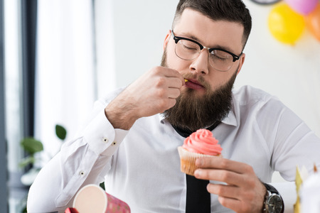 portrait of businessman holding birthday cupcake in hands in office Stock Photo