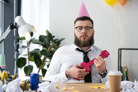 retrato, de, hombre de negocios, con, fiesta, cono, en, cabeza, y, juguete, guitarra, en, lugar de trabajo, en, oficina