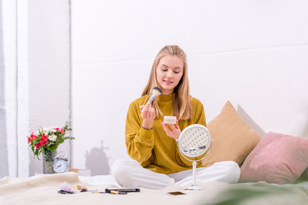happy young woman applying blush while sitting on bed at home Stock Photo
