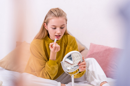 attractive young woman applying lipstick on bed at home Stock Photo