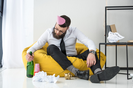 drunk businessman in formal wear with paper cone on head sitting on bag chair Stockfoto