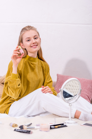 young woman with jar of nail polish sitting in bed at home