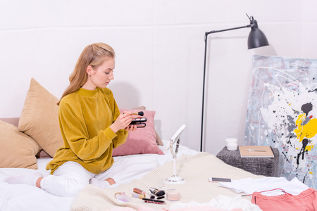 young woman doing makeup at home on bed