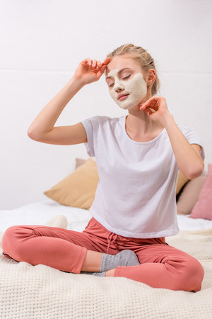 young woman with white clay facial mask sitting on bed at home Foto de archivo - 112756435