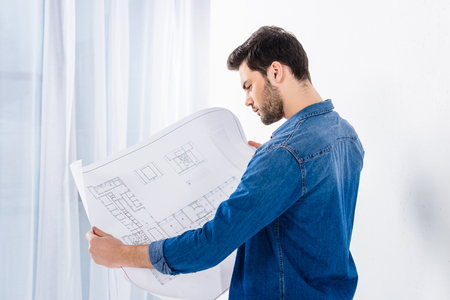handsome man looking at blueprint on white 写真素材