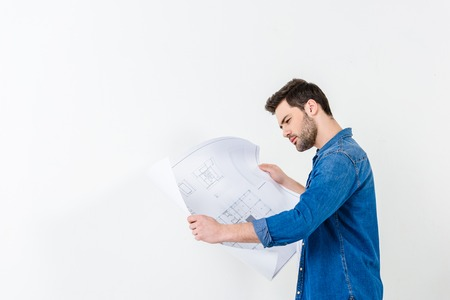 side view of man looking at blueprint isolated on white