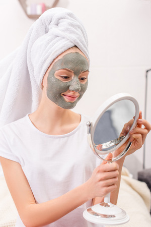 young woman with cosmetic clay mask looking at mirror at home Foto de archivo - 112756595