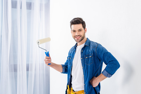 smiling man holding paint roll brush and looking at camera 写真素材