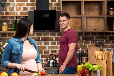 young pregnant woman and happy man looking at each other in kitchen