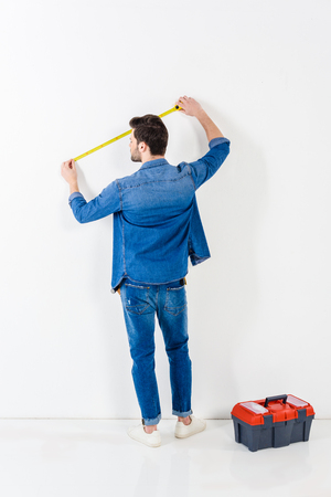 rear view of man measuring wall with tape measure on white Banco de Imagens
