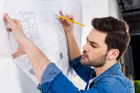 handsome architect writing on blueprint on white Banco de Imagens