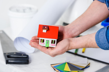 cropped image of man holding small house in hands