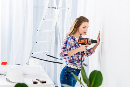 side view of girl drilling wall