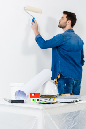 man painting wall with paint roll brush Banco de Imagens