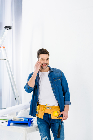 smiling man talking by smartphone and looking away