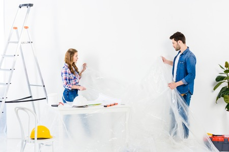 couple holding cellophane while making repairs at home Stock Photo