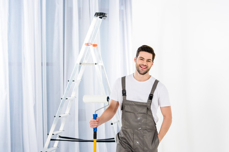 smiling handsome man standing with paint roller brush 写真素材