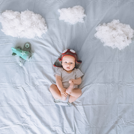 top view of dreamy infant child in knitted pilot hat with toy plane surrounded with clouds made of cotton in bed Stock fotó