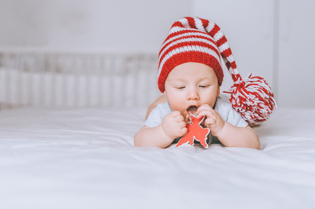 infant child in red and white striped hat with pompom playing with toy angel in bed
