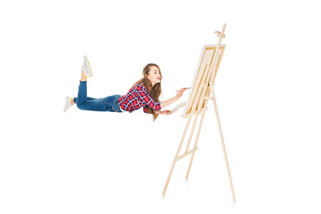 girl levitating and painting on easel isolated on white