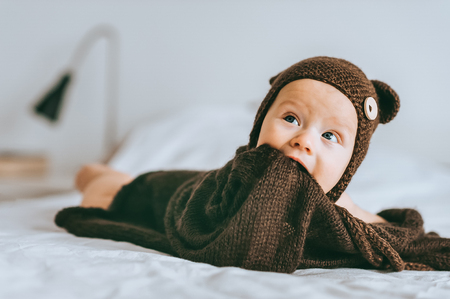 adorable infant child in brown knitted hat with blanket in bed