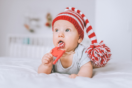 infant child in knitted striped hat playing with toy deer in bed