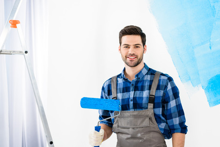 smiling man standing with paint roller brush and looking at camera