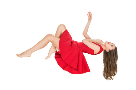 young woman in red dress falling with closed eyes isolated on white