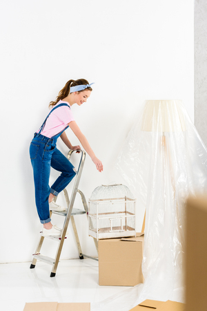 girl standing on ladder and taking bird cage Banque d'images - 112757072