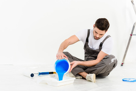 handsome man pouring paint into tray