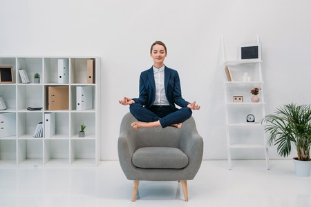 smiling young businesswoman meditating with closed eyes while levitating in office