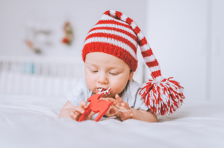 infant child playing with toy deer decoration in bed