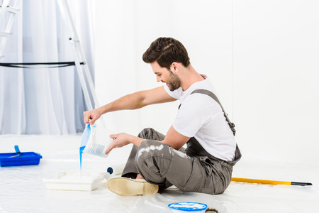 side view of handsome man pouring paint into tray