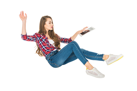 young woman using digital tablet while levitating isolated on white