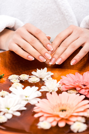 cropped view of woman making spa procedure with flowers, nail care concept