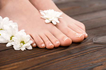 cropped view of feet with natural pedicure and flowers on wooden surface 写真素材