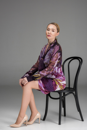 full length view of stylish kazakh woman sitting on chair and looking at camera on grey Stock Photo