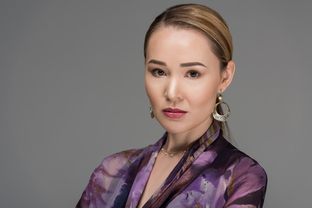 close-up portrait of beautiful kazakh woman looking at camera isolated on grey