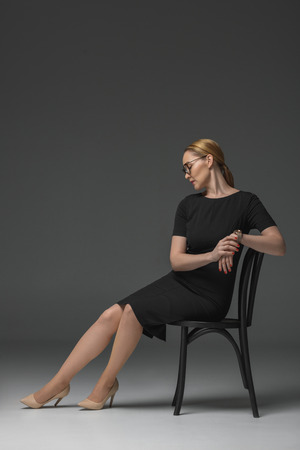 full length view of stylish kazakh woman in eyeglasses and fashionable black dress sitting on chair on grey Stok Fotoğraf