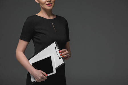 cropped shot of kazakh businesswoman holding digital tablet and clipboard isolated on grey