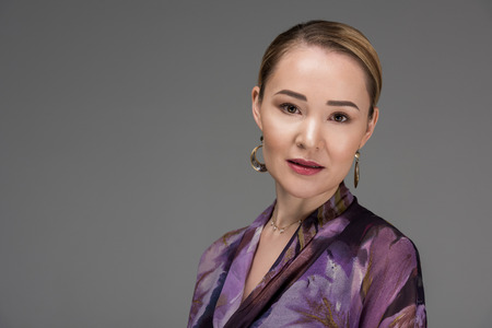 portrait of elegant stylish kazakh woman looking at camera isolated on grey
