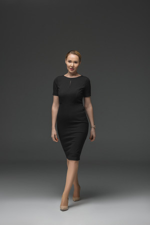 full length view of beautiful kazakh woman in black dress walking and looking at camera on grey