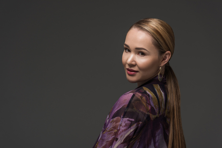 portrait of beautiful kazakh woman smiling at camera isolated on grey