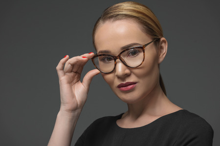 close-up portrait of beautiful kazakh woman in eyeglasses looking at camera isolated on grey