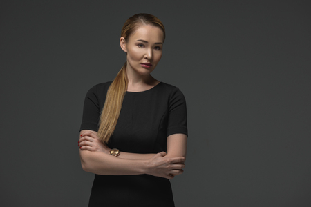 portrait of beautiful kazakh woman with crossed arms looking at camera isolated on grey Stok Fotoğraf - 112769567